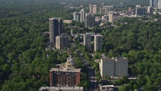 AX38_009 - 5K stock footage aerial video following Peachtree Road through condominium complexes and trees, Buckhead, Georgia