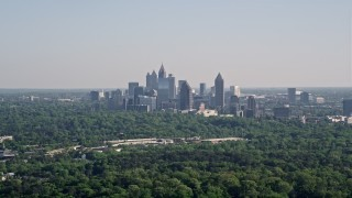AX38_027 - 5K stock footage aerial video of a distant shot of Midtown Atlanta skyscrapers beyond trees, Buckhead, Georgia