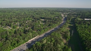AX38_032 - 5K stock footage aerial video orbiting an interstate with heavy traffic bordered by trees, West Atlanta, Georgia
