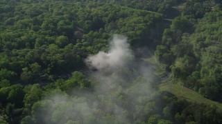 AX38_036 - 5K stock footage aerial video orbiting smoke from a burning home in a wooded area, West Atlanta