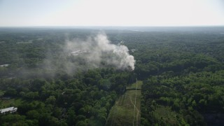 AX38_048 - 5K stock footage aerial video of smoke rising from a house fire in a wooded area, West Atlanta, Georgia