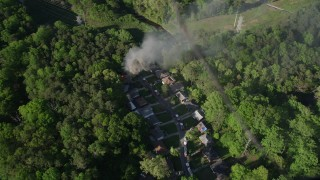 AX38_049 - 5K stock footage aerial video approaching smoke rising from a burning house in a wooded area, West Atlanta