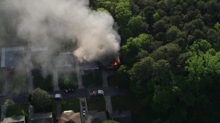 AX38_053 - 5K stock footage aerial video approaching a burning home with smoke rising and tilt down to a bird's eye, West Atlanta