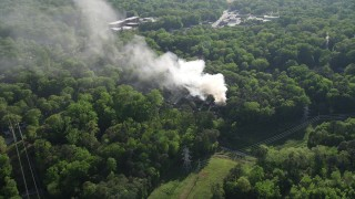 AX38_054 - 5K stock footage aerial video flying away from smoke from a burning house in a wooded area, West Atlanta