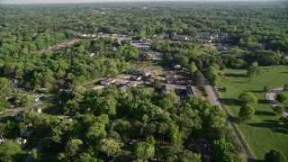 AX38_082 - 5K stock footage aerial video flying by abandoned buildings among trees, West Atlanta