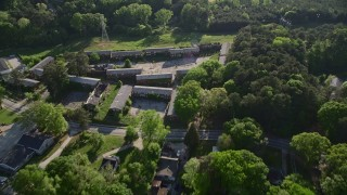 AX38_084 - 5K stock footage aerial video approaching abandoned buildings among trees, West Atlanta
