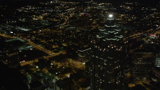 AX41_017 - 5K stock footage aerial video orbiting away from SunTrust Plaza revealing city lights, Downtown Atlanta, night