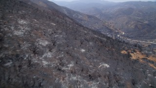 AX42_003 - 5K stock footage aerial video pan across scorched slopes of Santa Monica Mountains, California, and fly over them