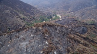 AX42_008 - 5K stock footage aerial video fly over scorched ridge of Santa Monica Mountains and approach an isolated rural home, California