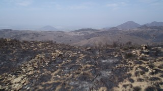 AX42_011 - 5K stock footage aerial video fly over a fire-damaged slope to reveal barren, less damaged Santa Monica Mountains, California