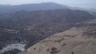 AX42_013 - 5K stock footage aerial video of destroyed rural homes near the edge of wildfire damaged slopes in the Santa Monica Mountains, California