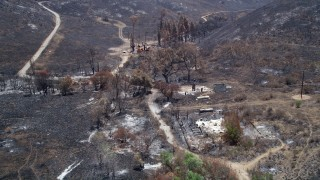 AX42_015 - 5K stock footage aerial video approach and fly over rural homes destroyed by wildfires in Santa Monica Mountains, California