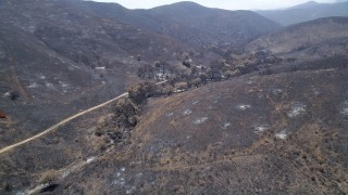 AX42_016 - 5K stock footage aerial video follow and pan across a mountain road through fire-ravaged Santa Monica Mountains, California