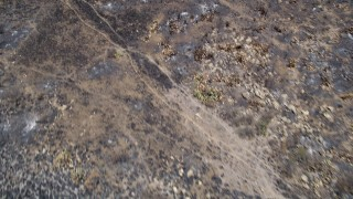 AX42_017 - 5K stock footage aerial video fly over charred slopes to reveal rural homes destroyed by wildfires, Santa Monica Mountains, California