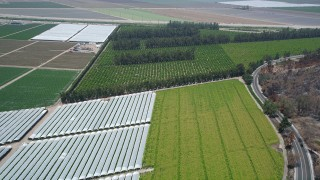 AX42_023 - 5K stock footage aerial video fly over crops and greenhouses to approach South Lewis Road, Camarillo, California