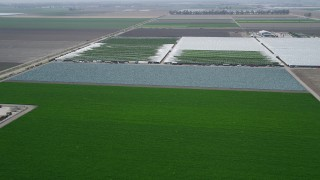 AX42_028 - 5K stock footage aerial video fly over crop fields and greenhouses, Camarillo, California