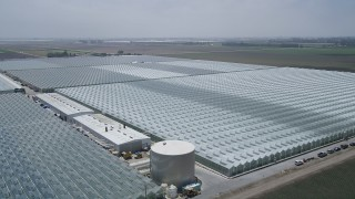 AX42_032 - 5K stock footage aerial video of flying by large greenhouses, Camarillo, California