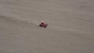 AX42_035 - 5K stock footage aerial video track a tractor tilling a field, Camarillo, California