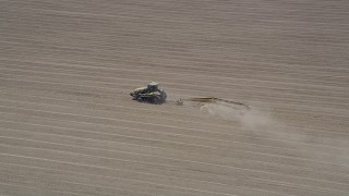 AX42_039 - 5K stock footage aerial video approach and track a tractor tilling a field, Camarillo, California