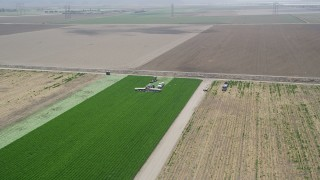 AX42_044 - 5K stock footage aerial video of flying away from farm workers working a crop field, and reveal second group, Camarillo, California