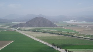AX42_047 - 5K stock footage aerial video flyby farmland and country roads around a steep hill, Camarillo, California