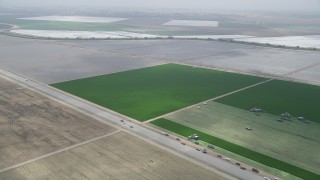 AX42_049 - 5K stock footage aerial video flyby a green feeds and tractors beside a country road, Camarillo, California