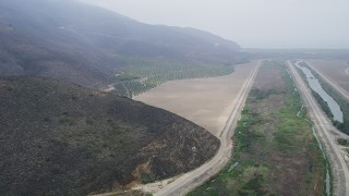 AX42_050 - 5K stock footage aerial video follow a country road to approach crops and farmland in light fog, Point Mugu, California