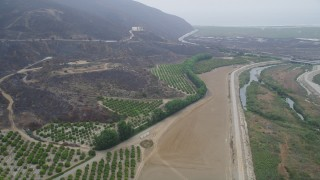 AX42_052 - 5K stock footage aerial video approach orchards at the base of mountains near a country road, Point Mugu, California
