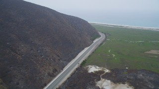 AX42_054 - 5K stock footage aerial video of following coastal Highway 1 with light traffic toward the ocean, Point Mugu, California