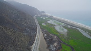 AX42_055 - 5K stock footage aerial video of following Highway 1 around a mountain to reveal a beach and marshland,  Point Mugu, California