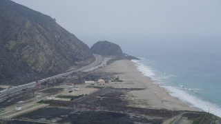 AX42_057 - 5K stock footage aerial video of following Highway 1 over an empty beach toward a rock formation, Point Mugu, California