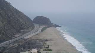 AX42_058 - 5K stock footage aerial video fly over a beach toward a giant rock formation, and pan around the bend, Point Mugu, California