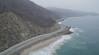 AX42_059 - 5K stock footage aerial video of following low over the coast beside Highway 1, Point Mugu, California