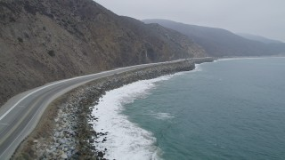AX42_060 - 5K stock footage aerial video fly low to follow light traffic on Highway 1, Point Mugu, California