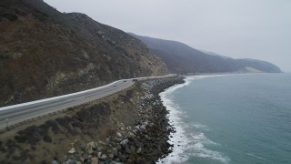 AX42_061 - 5K stock footage aerial video fly low over ocean waves by Highway 1 with light traffic, Point Mugu, California