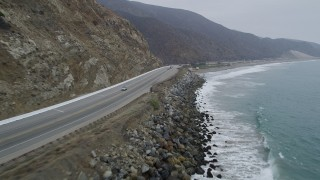 AX42_062 - 5K stock footage aerial video of flying low over waves and following coastal Highway 1, and pan to ocean, Malibu, California