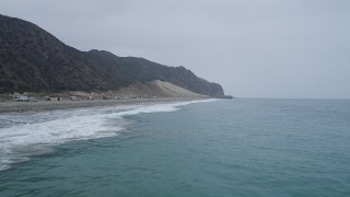 AX42_065 - 5K stock footage aerial video of flying low over Pacific Ocean waves and fly toward the end of a beach, Malibu, California