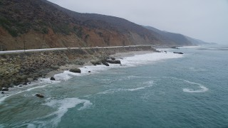 AX42_072 - 5K stock footage aerial video fly low over ocean waves beside Highway 1 with light traffic, Malibu, California