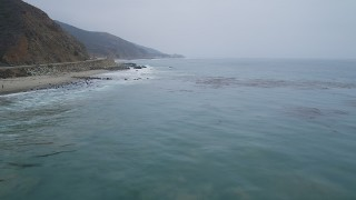 AX42_074 - 5K stock footage aerial video fly low over ocean kelp to approach waves crashing into the coast, Malibu, California