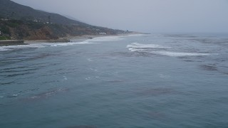 AX42_080 - 5K stock footage aerial video fly low over the ocean to approach waves rolling toward a beach, Malibu, California