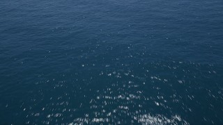 AX42_094 - 5K stock footage aerial video of flying low over crystal blue ocean waters, Malibu, California