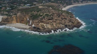 AX42_095 - 5K stock footage aerial video tilt from the ocean to reveal and approach the rugged cliffs of Point Dume, Malibu, California