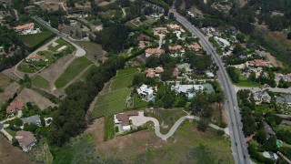 AX42_096 - 5K stock footage aerial video tilt to a bird's eye view of mansions and vineyards in the hills, Malibu, California
