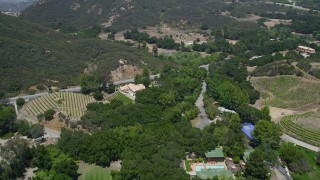 AX42_100 - 5K stock footage aerial video of flying over mansions, vineyards, and a country road in Malibu, California