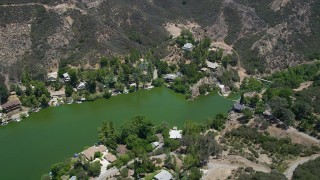 AX42_114 - 5K stock footage aerial video fly over Malibu Lake and tilt to lakefront homes on the shore, Agoura Hills, California