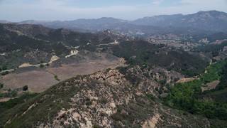 AX42_115 - 5K stock footage aerial video fly over Santa Monica Mountains to approach Mulholland Highway, California