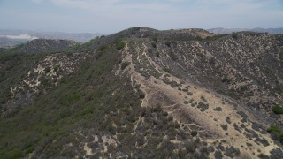 AX42_116 - 5K stock footage aerial video of flying low over ridges in the mountains, Santa Monica Mountains, California