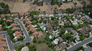 AX42_118 - 5K stock footage aerial video reverse view of tract homes with swimming pools in Calabasas, California