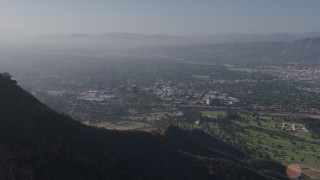 AX43_006 - 4K stock footage aerial video approaching, flying over Hollywood Sign, reveal Walt Disney Studios, Forest Lawn Cemetery in Burbank, Los Angeles, California