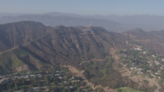 AX43_008 - 4K stock footage aerial video tilting from the Hollywood Reservoir to reveal and approach the Hollywood sign, Los Angeles, California